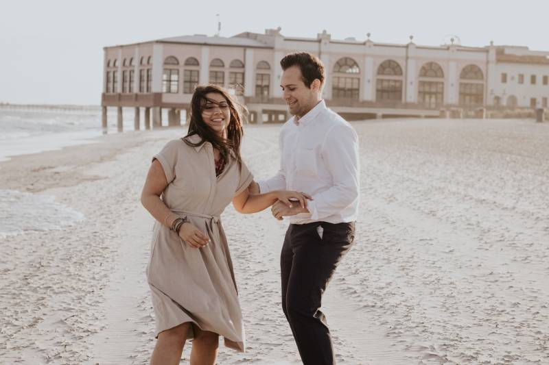 man holding woman hand's and shoulder on the beach