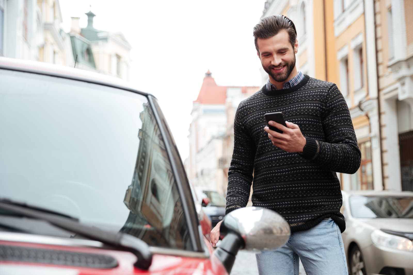 Portrait of a satisfied young man in sweater using mobile phone