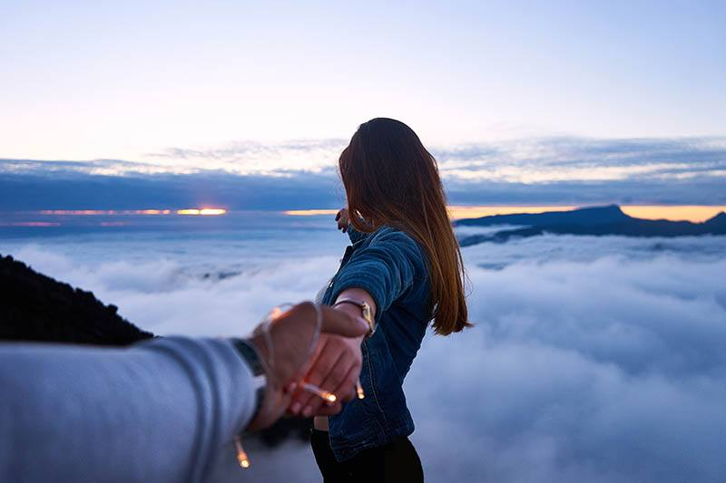 man holds woman's hand while she facing the sky
