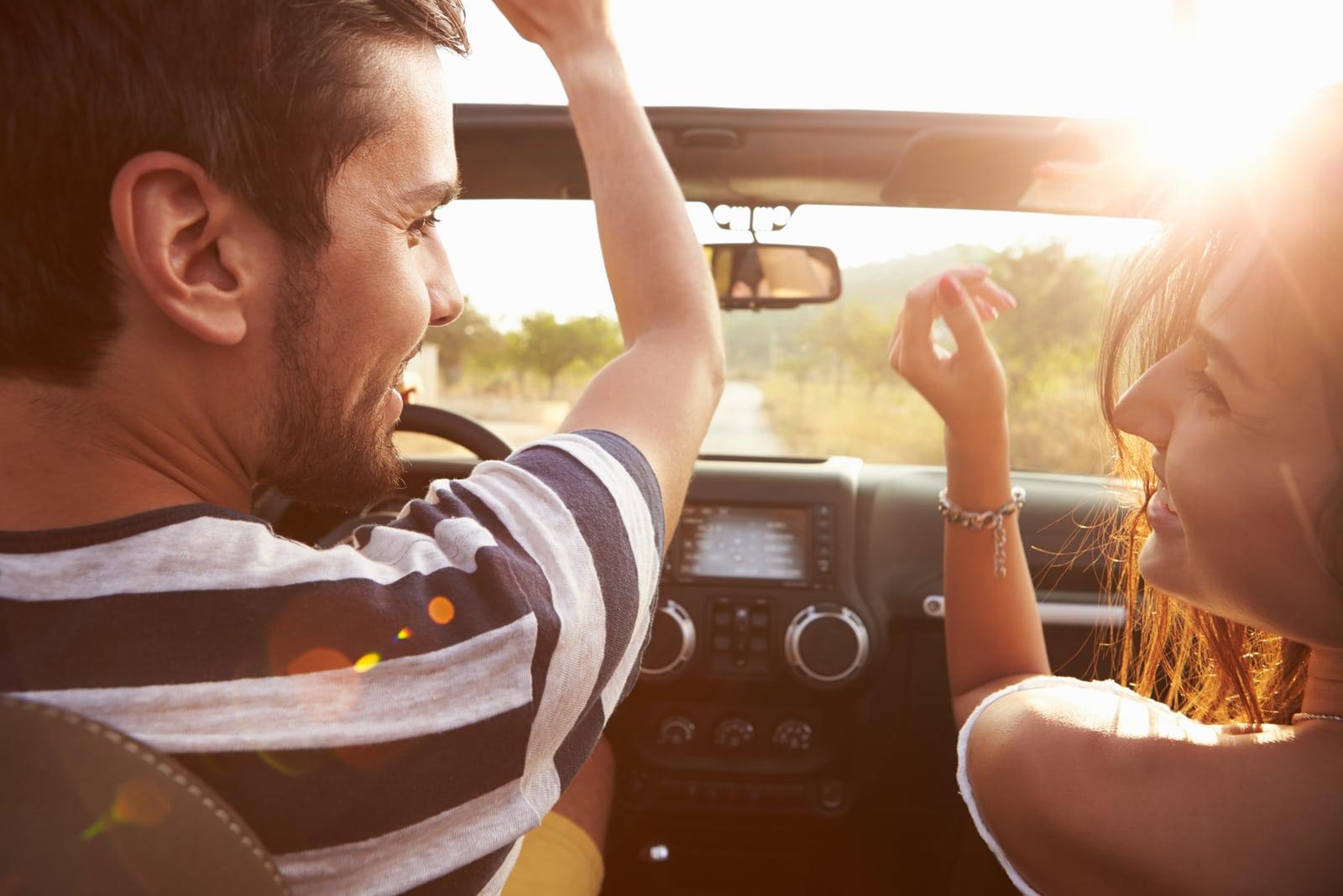 a loving couple enjoys driving a car