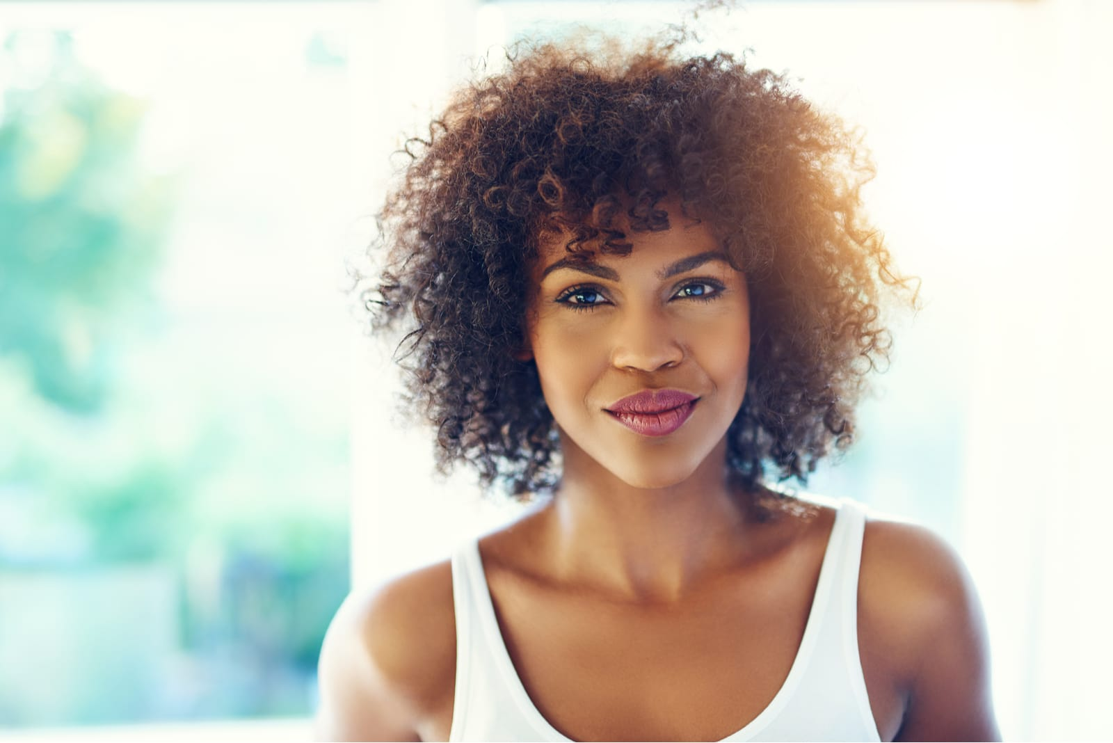 a portrait of an attractive black woman in a white undershirt