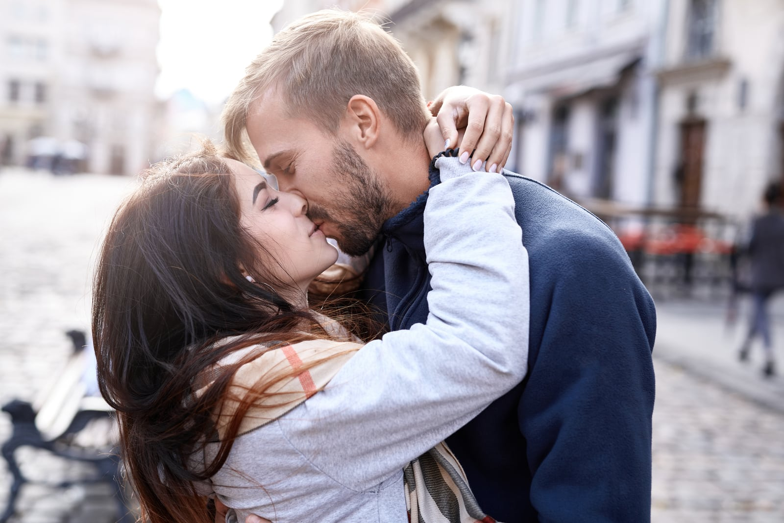 a romantic couple hugging and kissing on the street