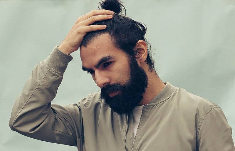 bearded man touching his hair