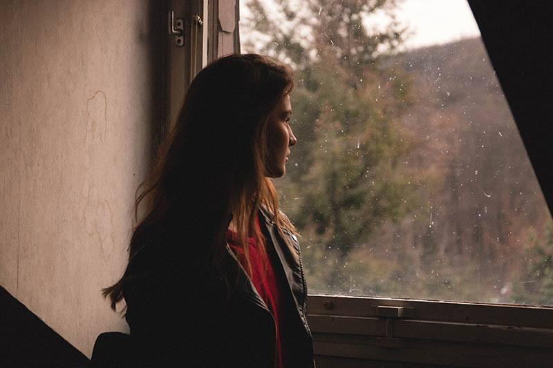 Woman looking sadly out of the window