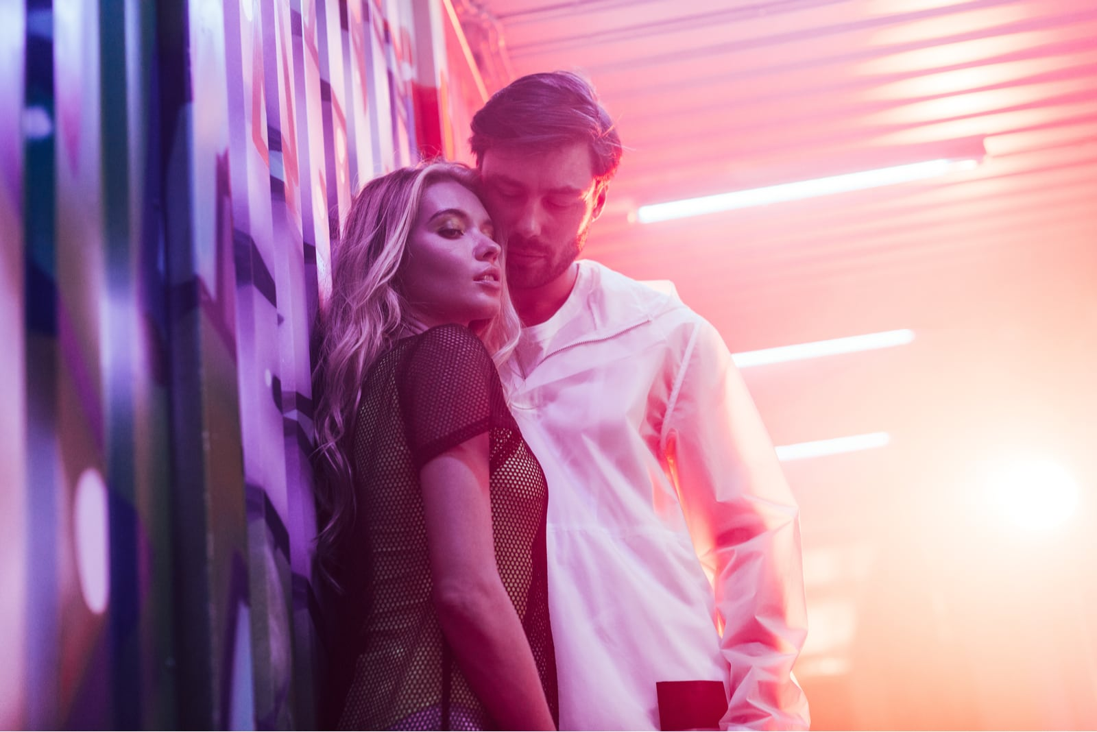 blonde woman hugging with handsome man in night club