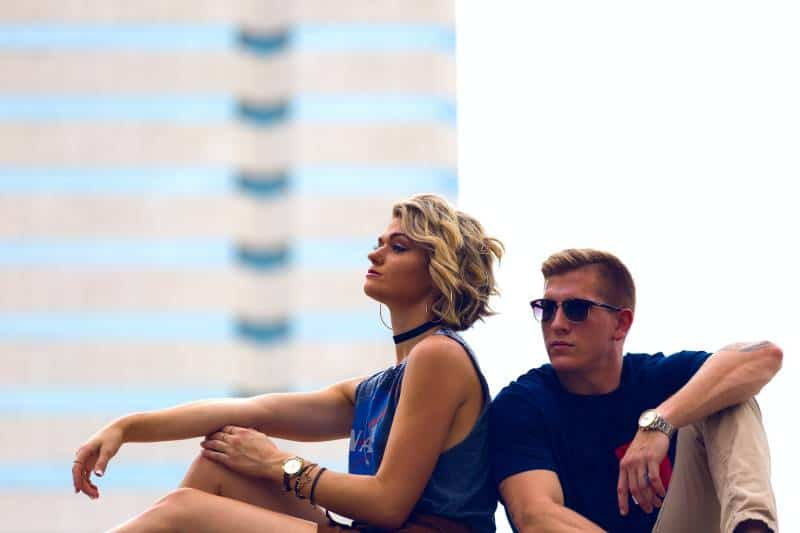 blonde woman with blue dress sits next to man with blue tshirt