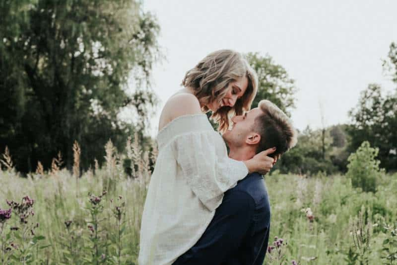 couple kissing each other around grass field