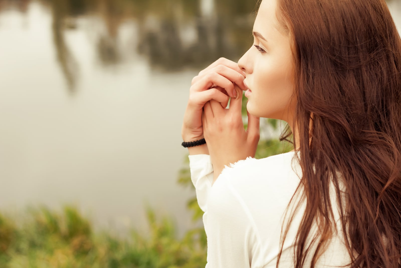 girl in profile near the lake in the summer