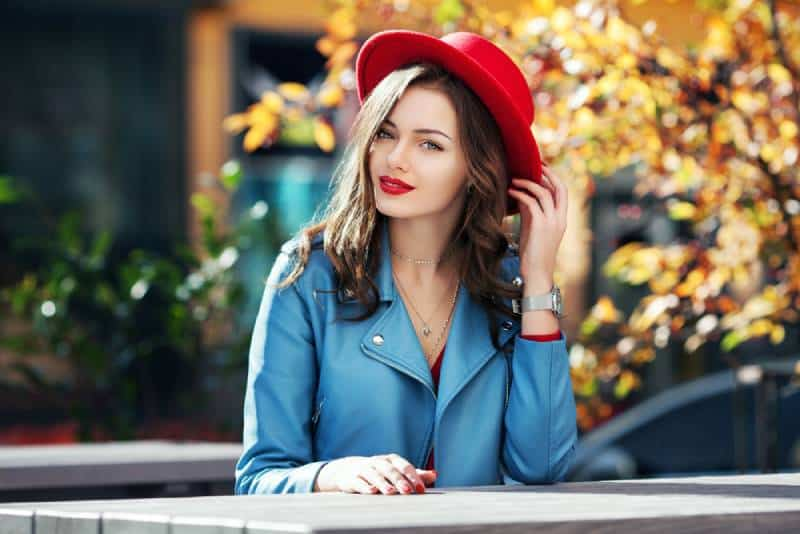 happy smiling girl with red lips wearing stylish red hat