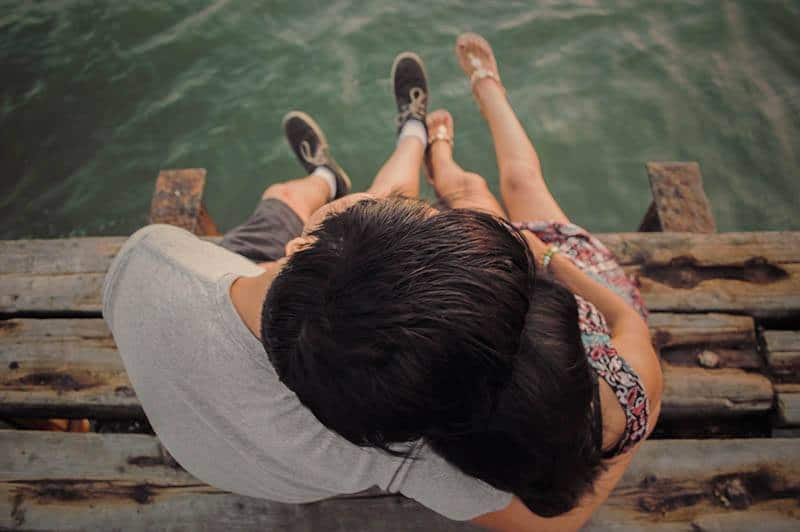 high angle of couple hugging on wooden dock