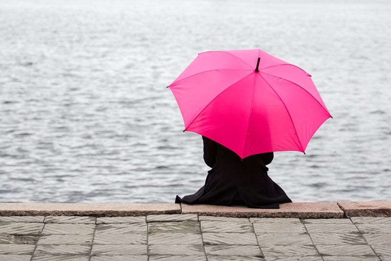 lonely woman sitting with pink umbrella outdoor