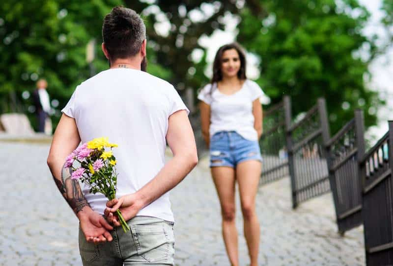 man holding flowers and waiting for girlfriend