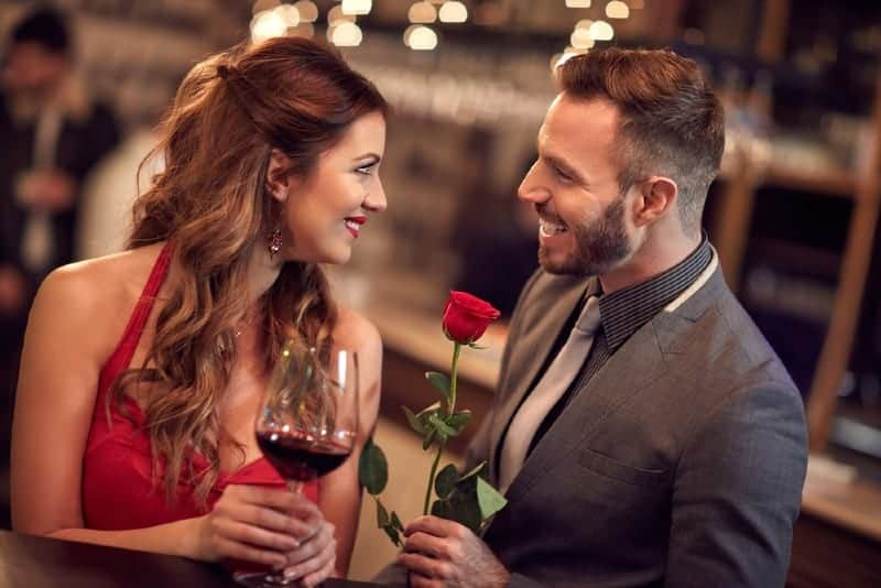 man holding roses standing in front of woman holding glass and looking each other