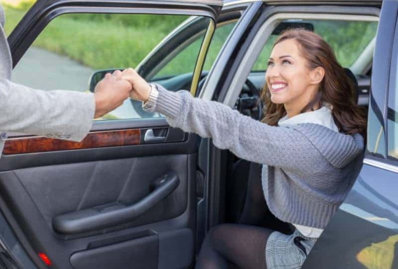 man holds smiling woman hand while she getting out of car