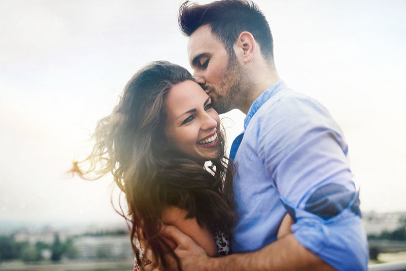 man kissing happy woman in the head