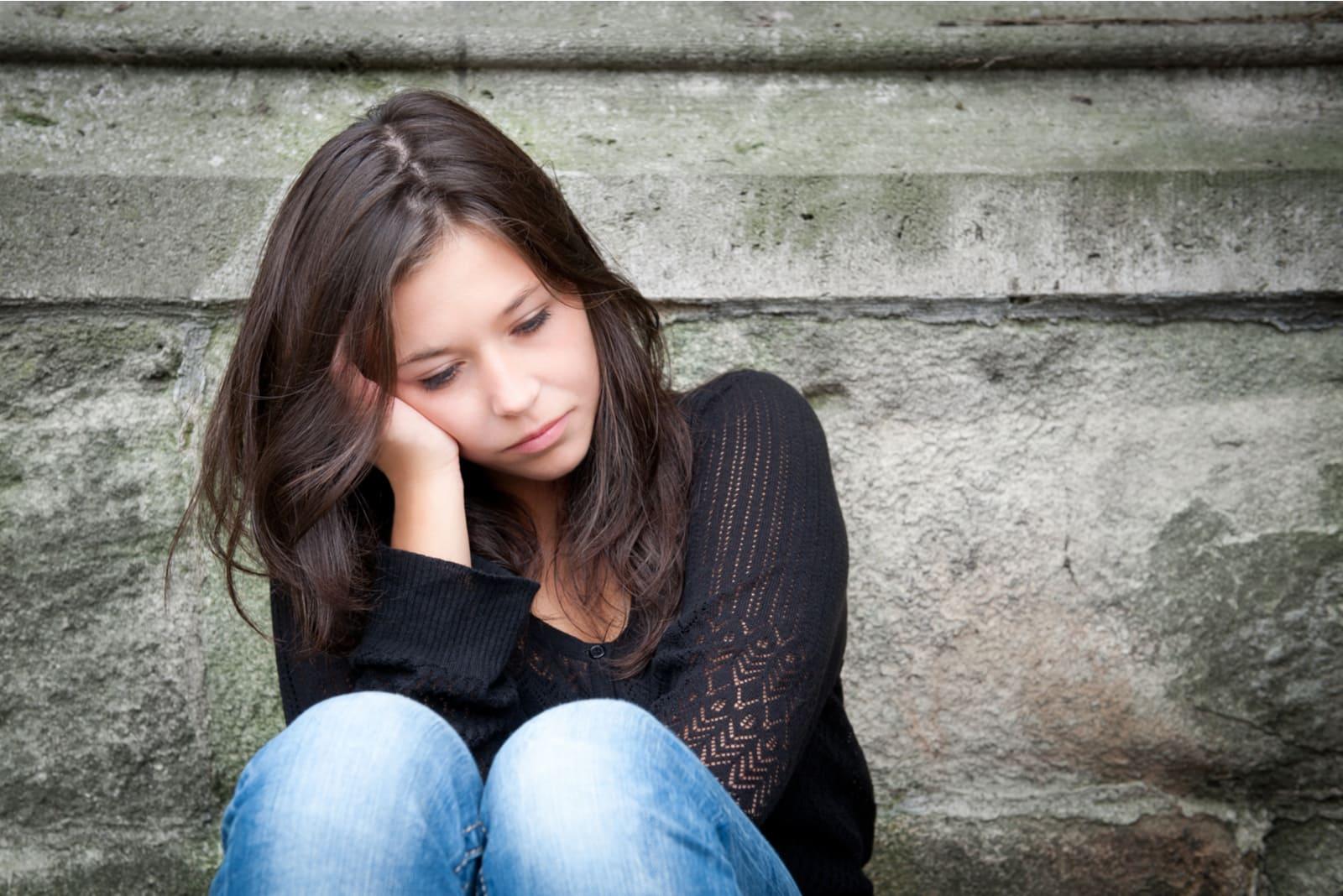 sad brunette sitting outside