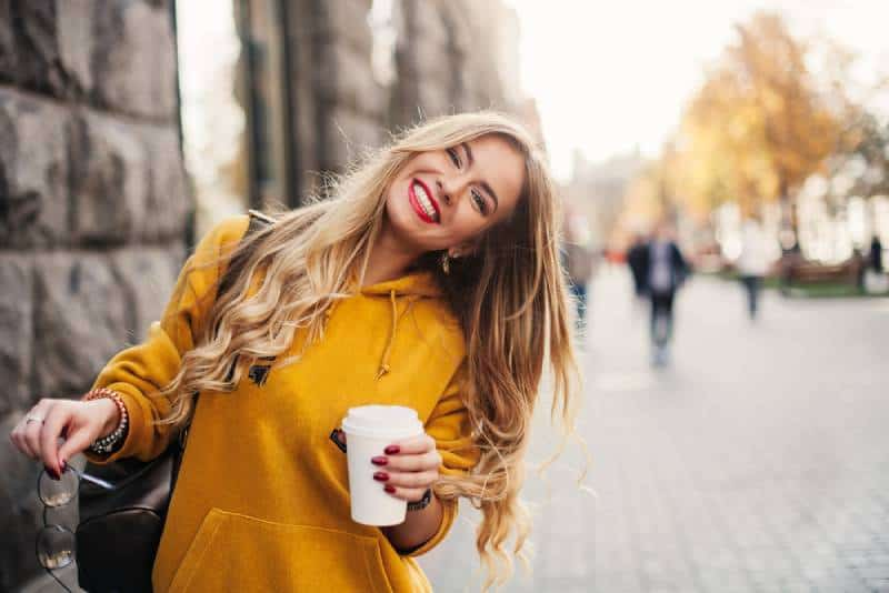 smiling woman in orange sweatshirt outside holding a cup