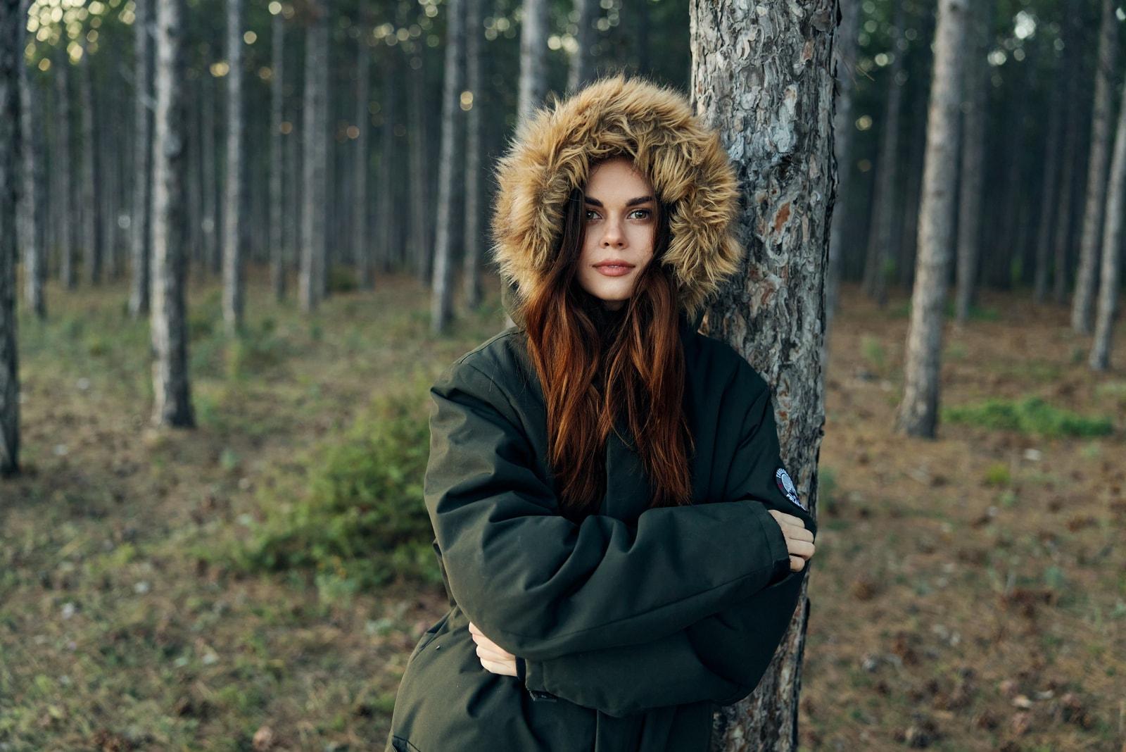 woman in warm jacket leaning on a tree