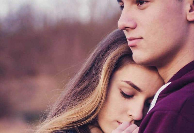 woman leaning on man chest outside