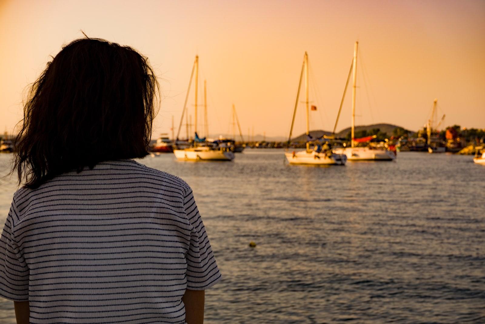 woman sitting alone on seaport coast at sunset