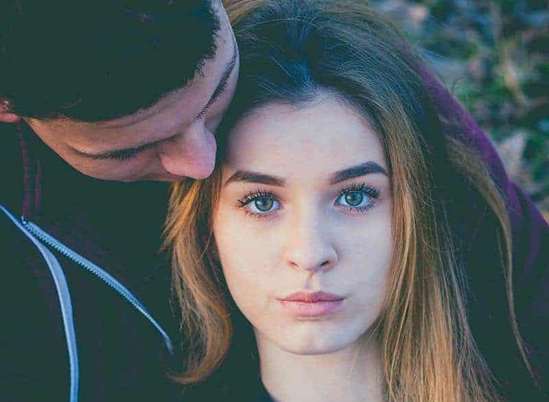 woman with blue eyes hugged by her boyfriend