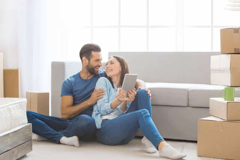 young couple in love sitting on floor at home and looking each other