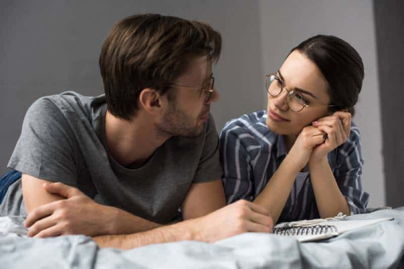 young couple lying in bed and looking at each other