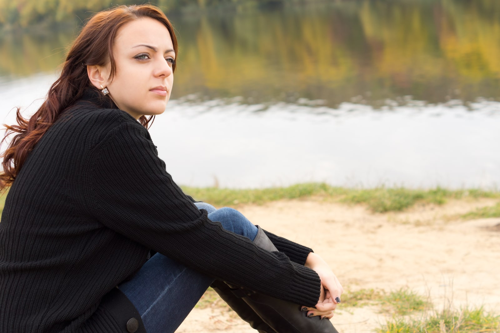 young woman sitting on a river bank