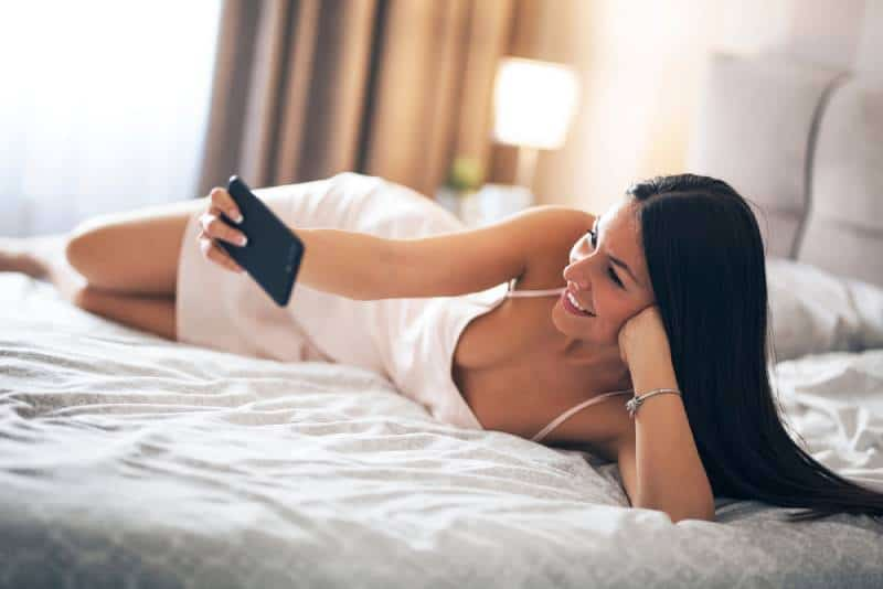 A beautiful smiling girl lying in bed in night dress and holding phone in her hand