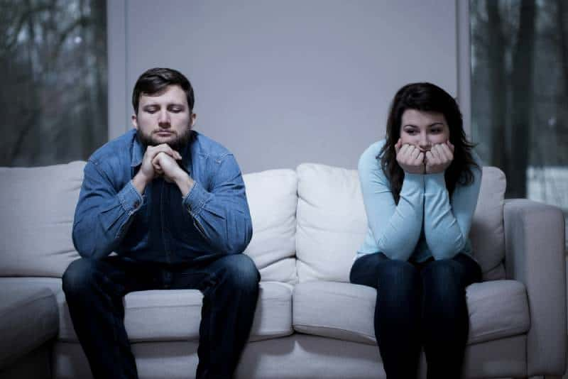 Couple sitting on sofa after argument