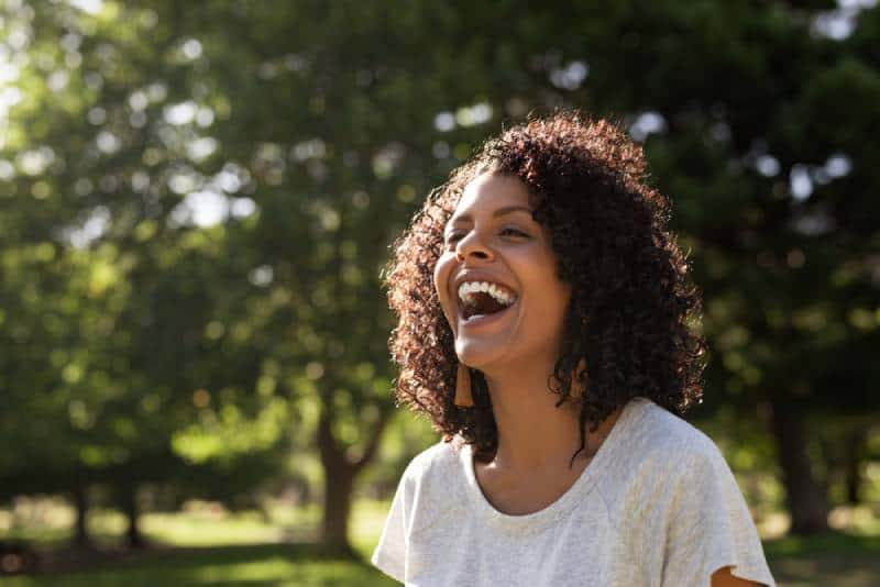 Laughing woman with curly hair while standing outside in a park