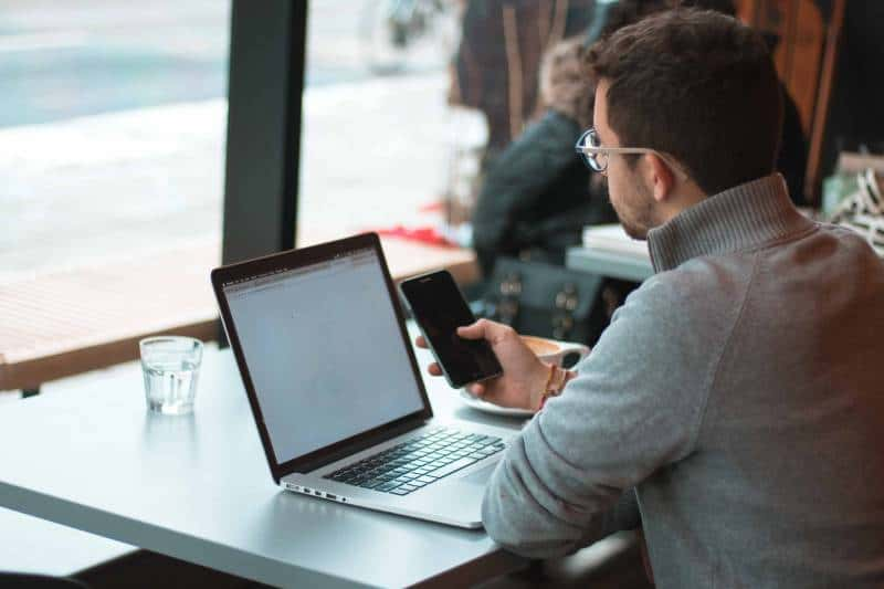 Man sitting near table with laptop and smartphone near window