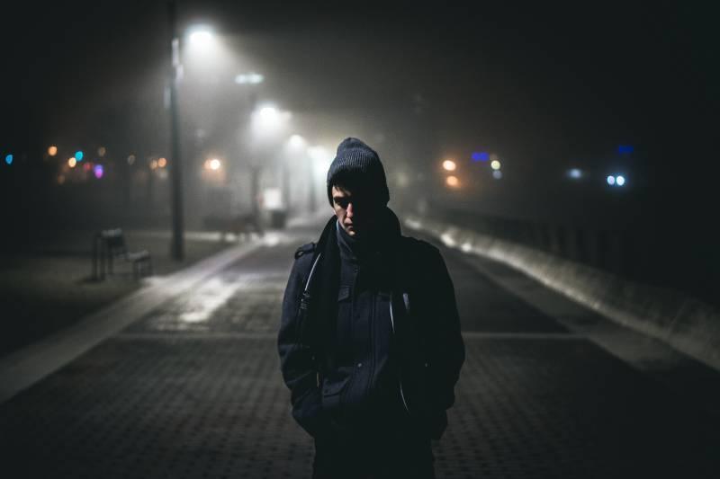 Man standing near street lamps during night