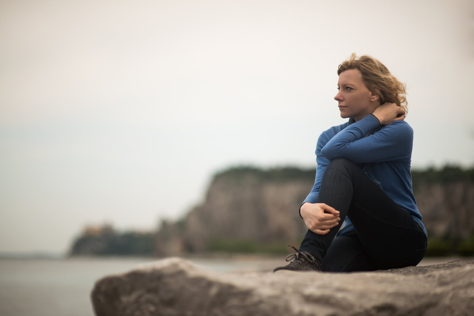 thoughtful woman sitting on a cliff