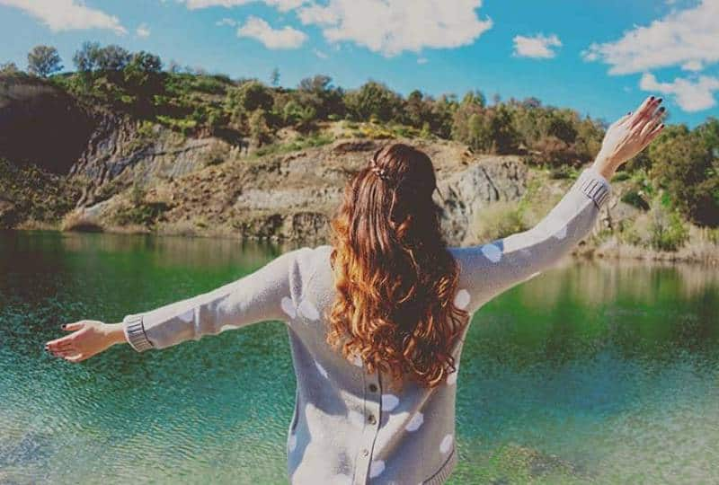 woman raising hand in front of water in nature