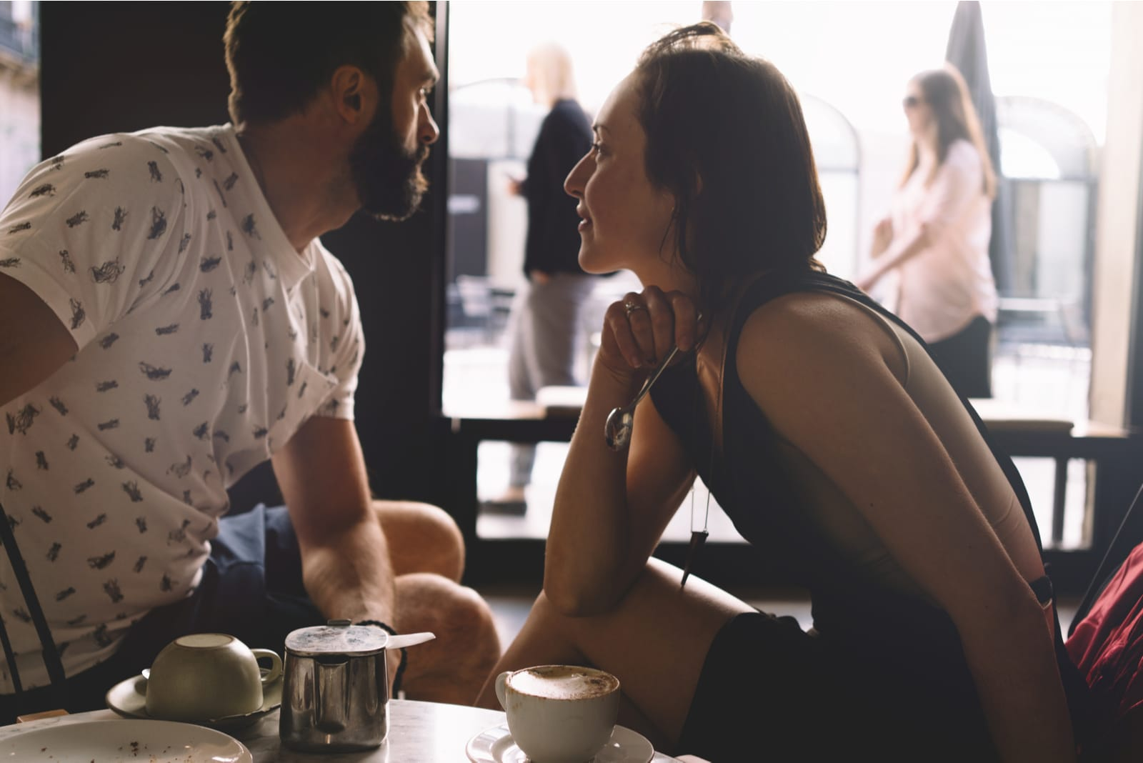 a man and a woman are sitting and drinking coffee in a cafe