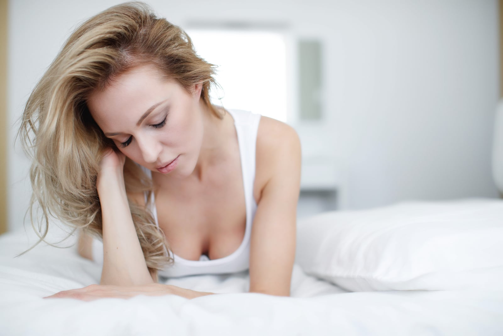 a sad blonde lying on the bed