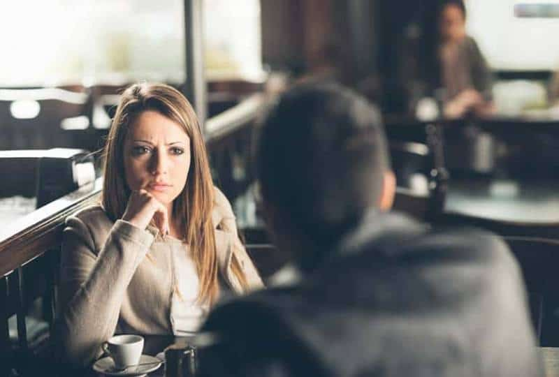 angry woman looking at man in cafe