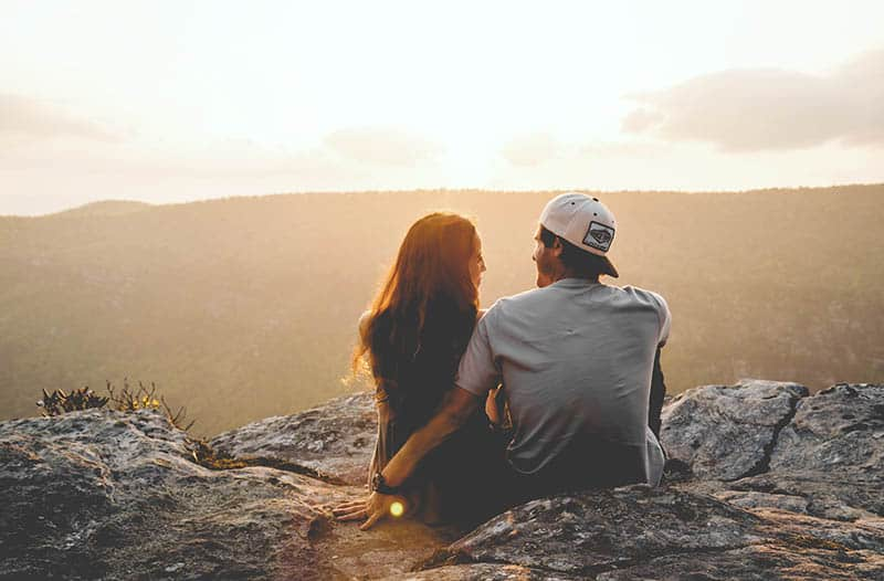 back view of couple sitting on hill