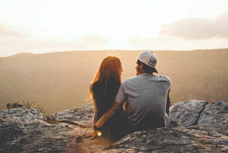 back view of couple sitting on mountain