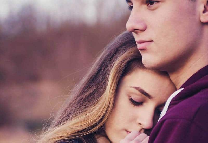 close up photo of woman puts her head on man chest outside
