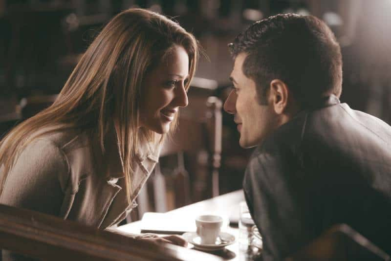 closeup photo of couple looking at each other at cafe