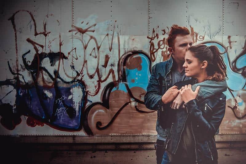 couple hugging near graffiti wall