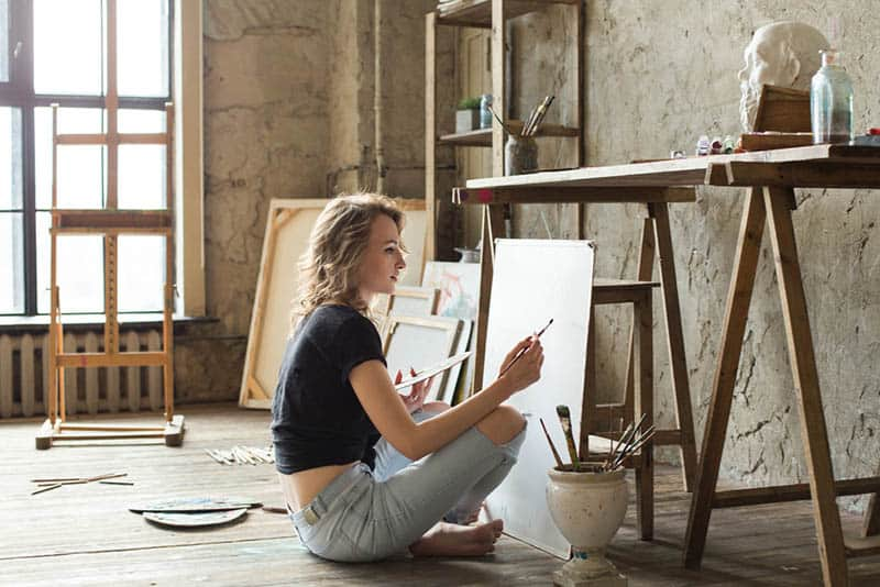 female sits and painting