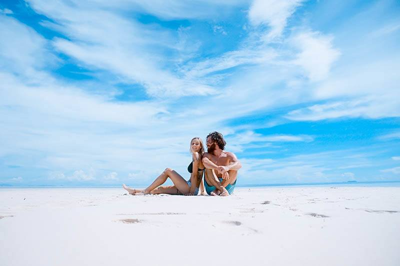 man and woman sitting on the beach during daytime