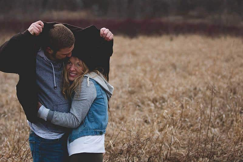 man covering woman's head with jacket on field