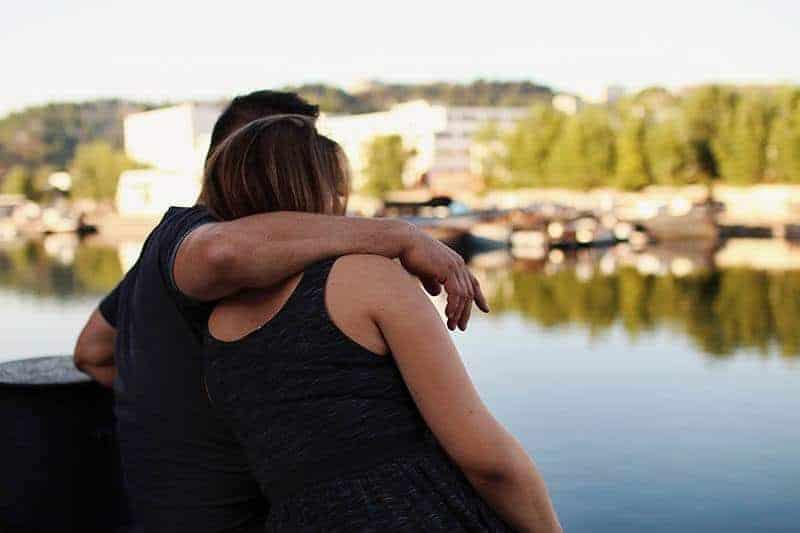 man hugging woman beside water