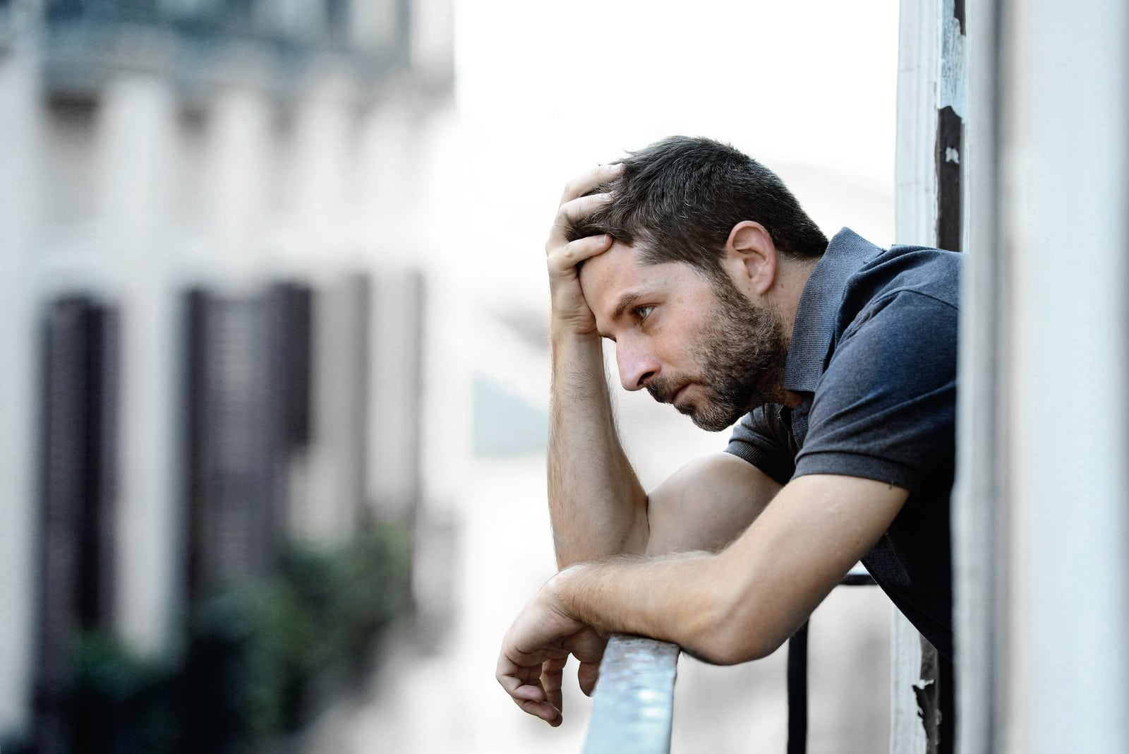 man outside at house balcony alone looking depressed