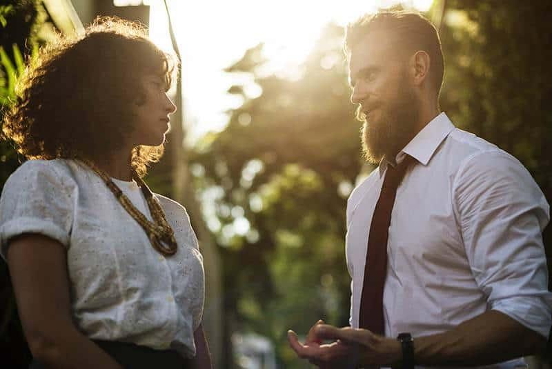 man wearing shirt looking at woman wearing dress and looks serious
