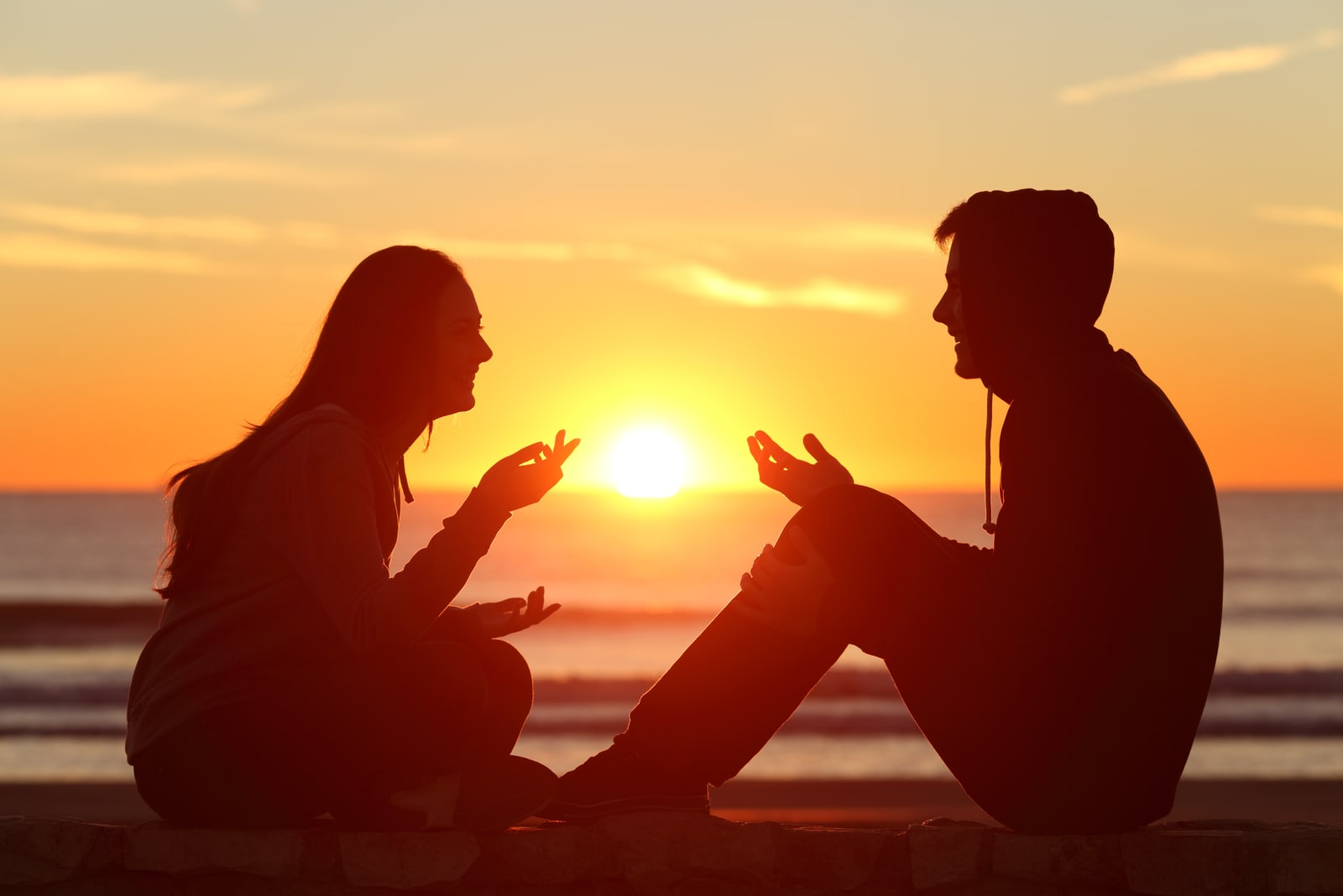 outside on a stone wall at sunset a man and a woman sit and talk